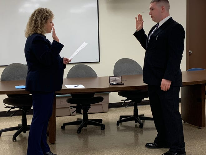 City of Mansfield Safety-Service Officer Lori Cope administers the oath of office to new Mansfield police Officer Raymond R. Reedy IV. Tuesday.