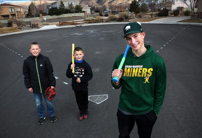 Aiden Brouhard, right, poses for a portrait with neighborhood kids Camden Bradfield,left, and his brother Sebastian in front of their makeshift baseball diamond at the end of Red Gulch Court in south Reno on Jan. 22, 2021.