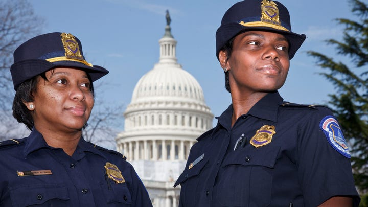 Acting Capitol Police Chief Yogananda Pittman, left, stands next to Monique Moore, right, in 2012 when they were promoted as the first two African-American women to rank of captain on the U.S. Capitol Police force.