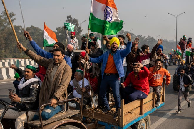 Protesting farmers riding tractors shout slogans as they march to the capital breaking police barricades during India's Republic Day celebrations in New Delhi, India, Tuesday, Jan. 26, 2021. Tens of thousands of farmers drove a convoy of tractors into the Indian capital as the nation celebrated Republic Day on Tuesday in the backdrop of agricultural protests that have grown into a rebellion and rattled the government.