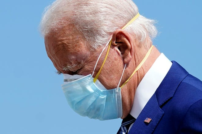 In this file photo, then-Democratic presidential candidate former Vice President Joe Biden wears two face masks as he arrives at Fort Lauderdale-Hollywood International Airport, in Fort Lauderdale, Fla., Oct. 13, 2020.