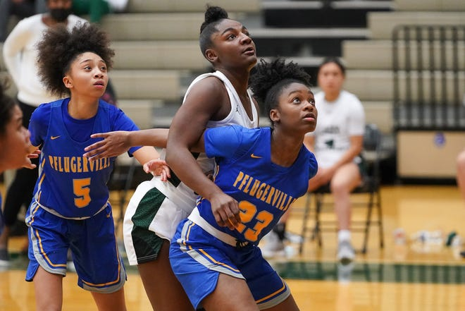 Pflugerville's Avari Berry, left, and Jordynn Watts, right, attempt to box in Connally's Lashiyah Fowler during Connally's 45-42 win Jan. 26 at Connally High School.