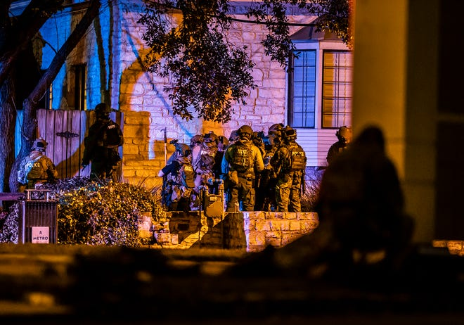 Members of the Austin police SWAT team gather outside a doctor's office in Central Austin where a hostage situation was reported Tuesday, Jan. 26, 2021. Two people were found dead inside the building, officials said.