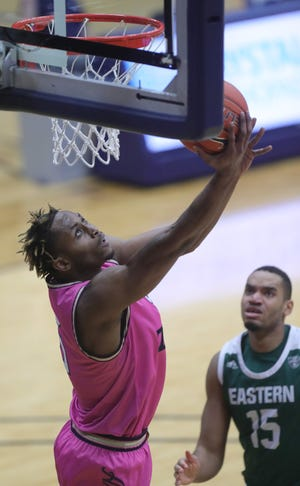 University of Akron's Camron Reece goes in for a first half basket in front of Eastern Michigan's Axel Okongo on Tuesday, Jan. 26, 2021 in Akron, Ohio, at James A. Rhodes Arena. [Phil Masturzo/ Beacon Journal]
