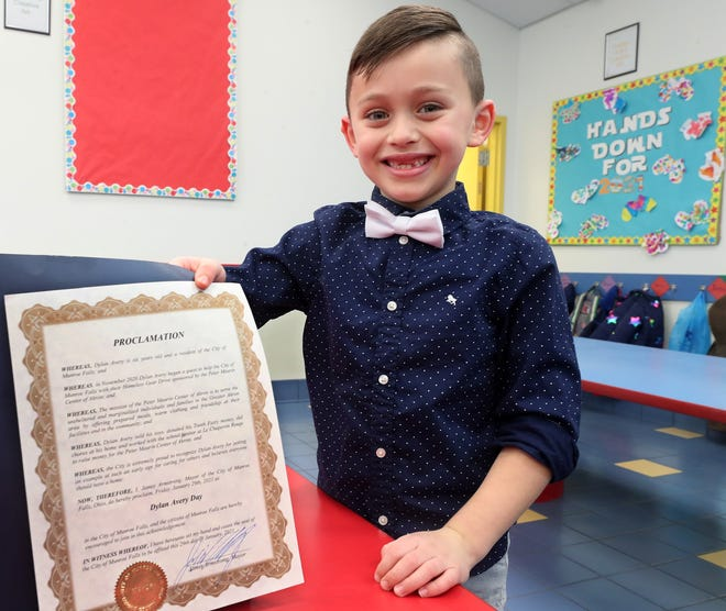 Dylan Avery, 6, of Munroe Falls, shows the proclamation from Munroe Falls honoring him for his efforts to help the homeless.