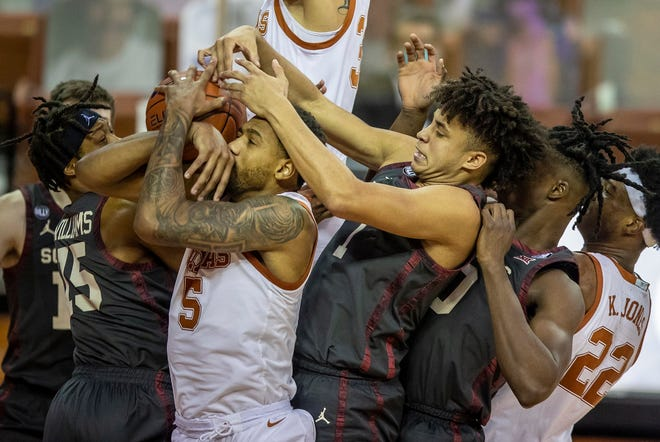 Texas Longhorns forward Royce Hamm Jr. (5) fights for the rebound against Oklahoma Sooners guard Alondes Williams (15) Oklahoma Sooners forward Jalen Hill (1) in the second half during an NCAA college basketball game at the Frank Erwin Center on Tuesday, Jan. 26, 2021
