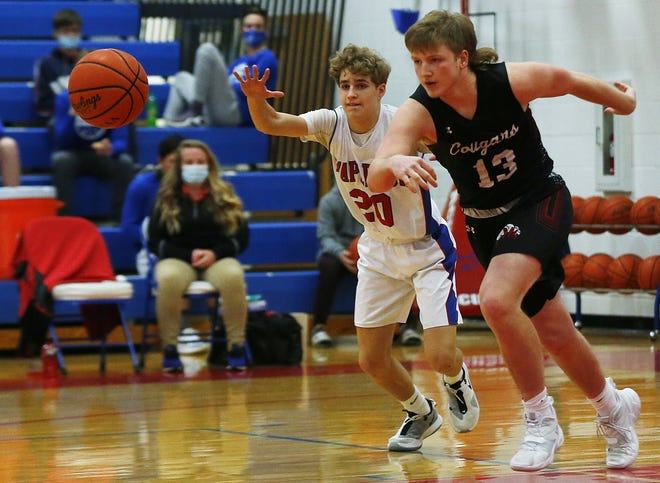 Mapleton's Kyle Sloter (20) and Crestview's Frank Ardis (13) chase after a loose ball Tuesday at Mapleton High School. The Cougars won, 64-35.