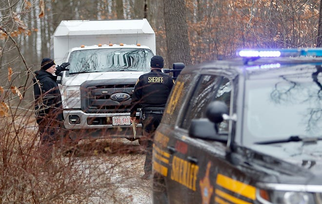 An Ohio BCI investigator talks with Ashland County Sheriff's Deputy Rick Kinter at the scene.