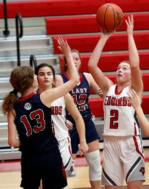 Loudonville's Corri Vermilya (2) puts up a shot against New Hope Christian Academy's Maren McCallister (13) during high school girls basketball action Tuesday at Loudonville High School. The Redbirds won, 90-32.