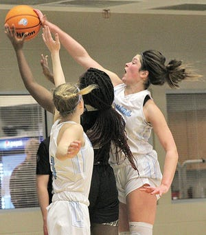 Bartlesville High School guard Kate Gronigan, right, gets her hand on the ball on a shot by a Broken Arrow High School player during varsity girls' basketball action Tuesday in Bartlesville. Broken Arrow won, 61-37.