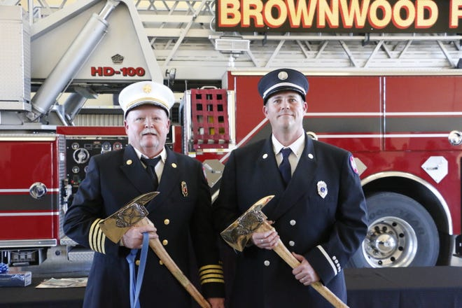 Retiring Brownwood fire service veterans Buddy Preston (left), assistant chief for fire prevention/investigations, and Lt. Ted Hull stand with the engraved fire axes they received at a retirement party Tuesday in the Central Fire Station.