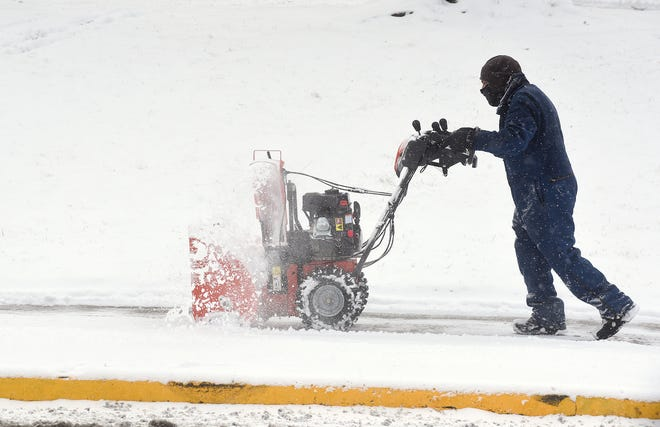 Mike Ide, custodian for the First Baptist Church, 1112 E. Broadway, removes snow from the sidewalk on Jan. 27 following overnight snowfall.