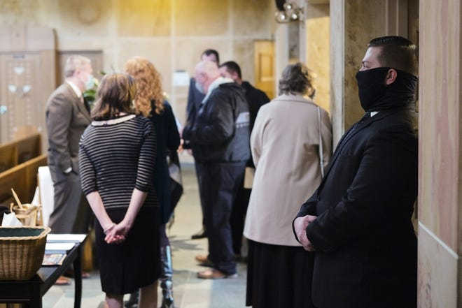 Michael Shanks, right, a funeral director with Egan-Ryan Funeral Service, stands as guests arrive before the funeral of Juliana Devine on Wednesday at St. Catharine Catholic Church in Bexley. Funeral directors in Ohio have been lobbying Gov. Mike DeWine for inclusion in Phase 1B of the state's COVID-19 vaccination plan, arguing that many of their workers are in contact with deceased COVID-19 patients and their family members in the normal course of their jobs.