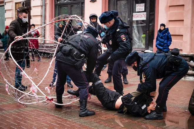 Police officers detain opposition activist Pavel Krysevich, on the ground, after his action in support of Russian opposition leader Alexei Navalny and against the mass arrests at Saturday's uncoordinated rally in Moscow, Russia, Sunday, Jan. 24, 2021. Krisevich locked himself in a sphere covered with barbed wire in Moscow's centre protesting the arrest of Russian opposition leader and mass detentions during Saturday's protests. Krisevich and several of other activists were detained shortly after the start of the action. (AP Photo/George Markov)