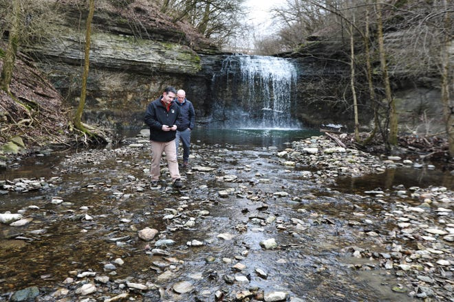 Metro Parks director Tim Moloney, left, and Thrive Companies President Mark Wagenbrenner walk around at the Millikin Ditch waterfall at Quarry Trails Metro Park, which is near Trabue and Dublin roads.