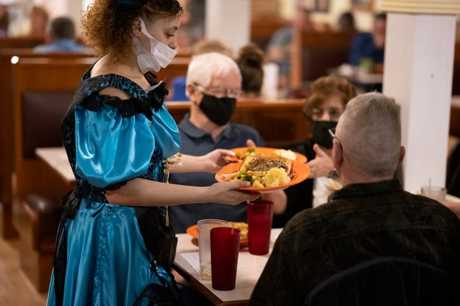 A waitress serves dinner to the people at the dinner show at Bloom's Bakehouse in Leesburg on Saturday night. [Cindy Peterson/Correspondent]