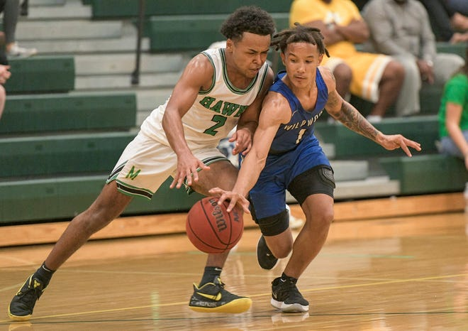 Wildwood's Nate Rembert (1) and Lake Minneola's Micah Thomas (2) battle for control of the ball during Tuesday's game at Lake Minneola. Wildwood won 63-62 in overtime.  [PAUL RYAN / CORRESPONDENT]