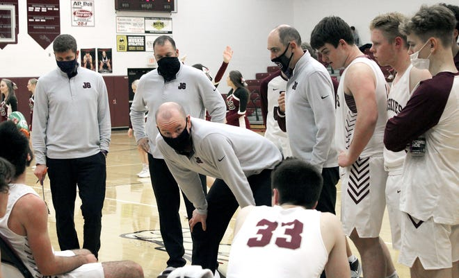 John Glenn head coach Eric Sheck, center, flanked by his coaching staff of Brian Fulks, Kevin Lahna and Chad Orecchio instructs his squad during a time-out during Tuesday's home court match-up with Meadowbrook.