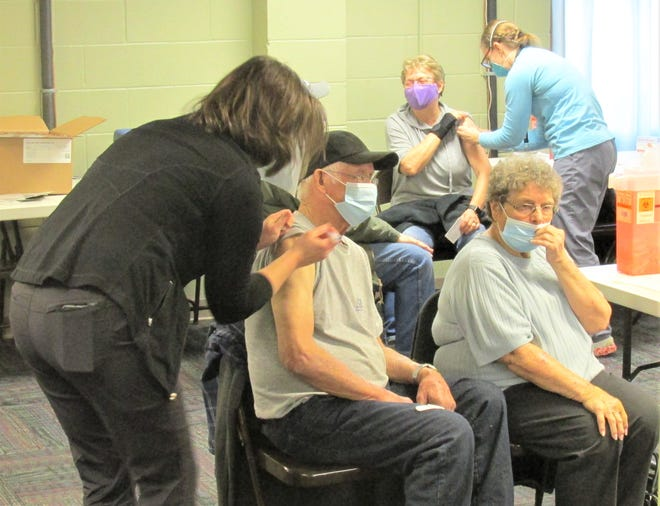 Larry VanSickle and his wife, Kay, were among the 100 senior citizens to receive the first dose of the COVID-19 vaccine on Wednesday at the Holmes County Senior Center in Millersburg. Inga Troyer was the nurse administering the vaccine to the VanSickles. In the background, Joyce Croskey received her vaccine from Holmes County Health Department nurse Raquel Miller.