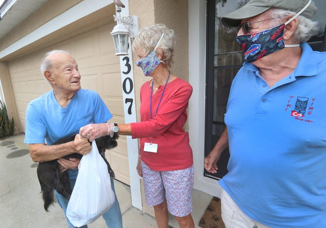 John Russo, at left, and Meals on Wheels drivers Sue and John Austin, talk at his Edgewater home as they drop off prepared meals.