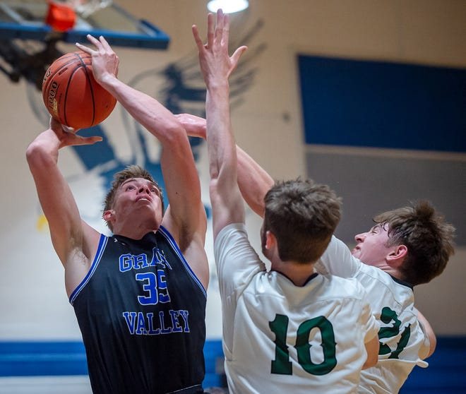 Grain Valley senior Cole Keller goes up for a contested shot against Barstow's Michael Singleton (10) and Aldan Lawlor (21) in their first-round game in the Grain Valley Sonic Showdown Tuesday. Keller amassed 28 points and 16 rebounds to lead the Eagles to a 58-47 win over the Knights.