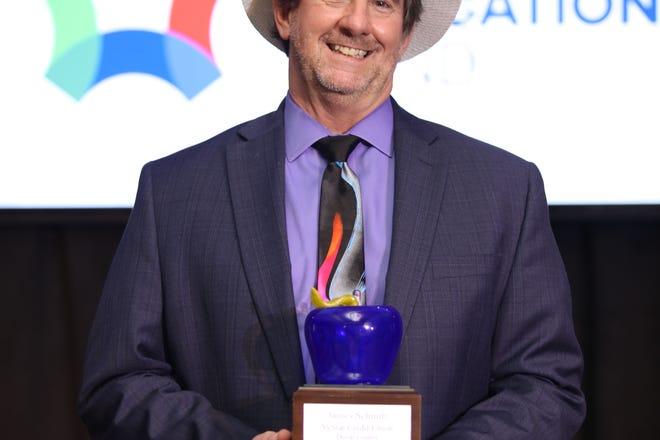 Jim Schmitt receives his Teacher of the Year title at the Eddy Awards