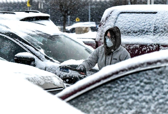 Sonja Jantz uses a snow scraper to clean off her car Tuesday in a Garden City High School parking lot during a period of snowfall. The latest winter storm will be short-lived as high temperatures are forecast in the 50s by the end of the week.