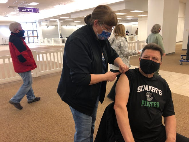 Fort Hays State University custodian Frank Mindrup, of Hays, receives COVID-19 vaccine Tuesday afternoon from Holly Bittel, a registered nurse at HaysMed, at the former Gordmans retail store in Big Creek Crossing mall.