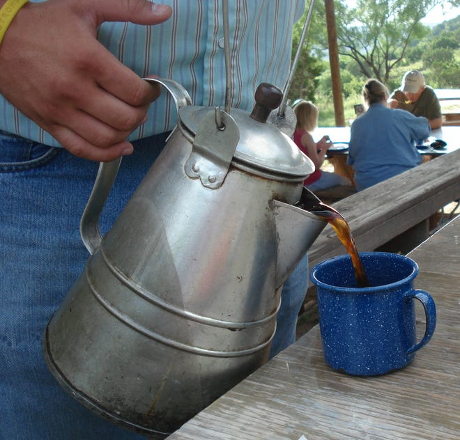 """During an outdoor breakfast at Elkins Ranch, Palo Duro Canyon, TX, a real cowboy """"hots up"""" Janie Mae's coffee. They serve cowboy-style coffee made without strainers inside the huge pot."""