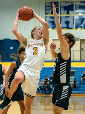 Hutchinson's Jake Huhs (2) drives to the basket past Wichita Trinity Academy's Rowan Gerber (22) Tuesday night at the Salthawk Activity Center. Hutchinson defeated Wichita Trinity Academy 62-58.