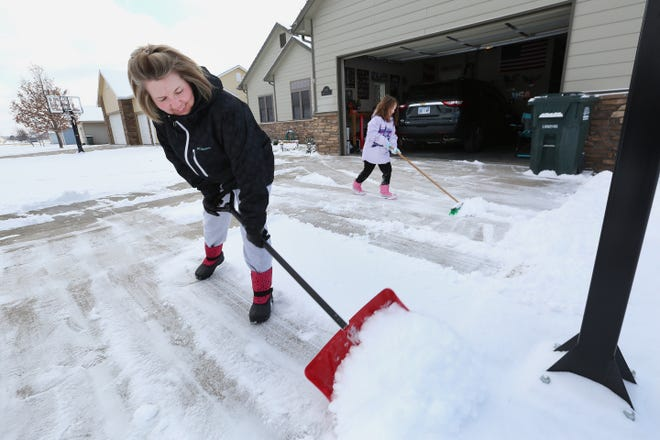 Melissa Imler shovels snow off the driveway with her 7-year-old daughter, Makenna Imler, Wednesday morning on E. Kisiwa Village Road. Makenna had also created a snow angel and started on a snowman but found the snow was too powdery to compact well.