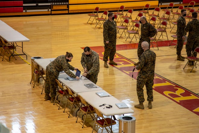 Service members with Marine Corps Installations East-Marine Corps Base Camp Lejeune set up stations for a COVID-19 vaccination center to support II Marine Expeditionary Force (II MEF) at Goettge Memorial Field House, Jan. 21.