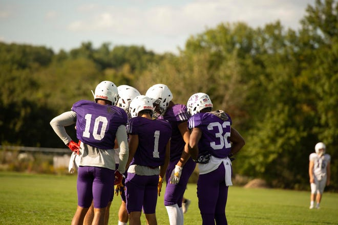 Members of the Western Illinois football team huddle during practice.