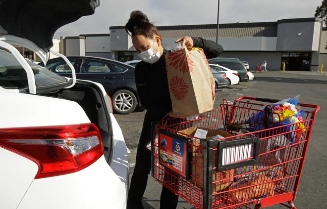 Instacart worker Saori Okawa loads groceries into her car for home delivery in San Leandro, California, in July. Many new gig workers aren't aware of the tax obligations associated with their new status as independent contractors. Delivery drivers, grocery runners and freelancers need to pay income and self-employment tax on their earnings, which can amount to 30% of their earnings. [AP File Photo/Ben Margot]