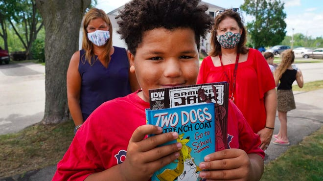 Mateo Fitzgerald, an incoming Portsmouth fifth-grader photographed during the summer of 2020, smiled with new books delivered by his teachers, New Franklin Elementary School reading specialist Donna Turco, left, and Principal Joanne Simons.