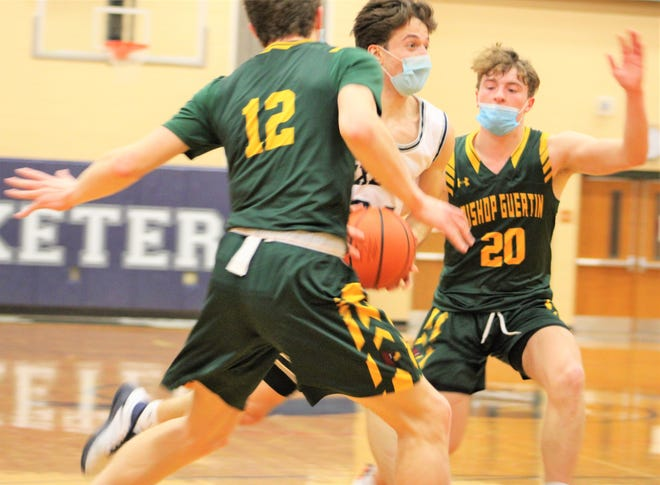 Exeter's Tom Delgado (24) drives between Bishop Guertin's John Sullivan (12) and Matt Santosuosso (20) in the second half of Tuesday's Division I boys basketball game.