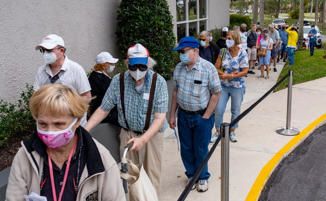 Seniors stand in line to make an appointment to receive the Moderna COVID-19 vaccine outside the King's Point clubhouse in Delray Beach, Florida on December 30, 2020. GREG LOVETT/PALMBEACHPOST