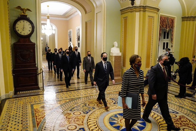 The Democratic House impeachment managers, led by Clerk of the House Cheryl Johnson and acting House Sergeant-at-Arms Tim Blodgett, walk through the Capitol to deliver to the Senate the article of impeachment alleging incitement of insurrection against former President Donald Trump, in Washington, on Monday.