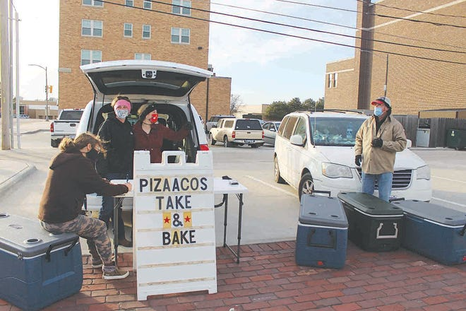 Pratt customer Kathy Hitz picks up her order of pizaacos at Merchants Park on January 20 from Dani Collins (business owner, standing left) and Morgan Shore, from Hutchinson. The pair, assisted by Dani's father, Dan Hoffman (right) make regular deliveries to Pratt each month from their restaurant in Hutchinson, called Pizaacos.