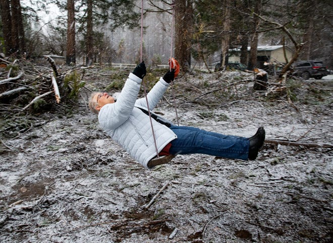 Artist Margaret Godfrey takes a ride on a tree swing that survived the flames of the Holiday Farm Fire despite the loss of the family home just feet away.