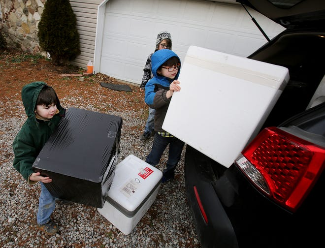 Wesley Hockinson, 4, Justin Hockinson, 7, and Cameron Hockinson, 10, help their grandma by loading the feral cat shelters into her car for delivery in the Alliance area.