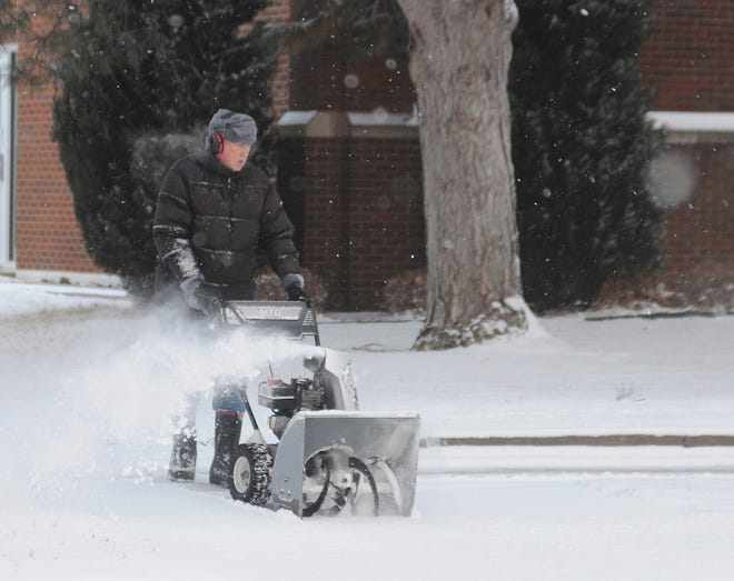 Kent Moon, maintenance worker for St. John's Lutheran Church, pushes a snow blower Wednesday morning to clear the 2 inches of snow off of the sidewalk next to the St. John's Lutheran Church, 302 S. 7th Street, in Salina.