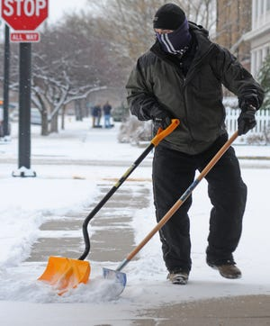 Chiropractor Brett Pennington uses two snow shovels Wednesday morning to remove the 2 inches of snow off of the sidewalk in front of the Pennington Chiropractic Center, 204 W. Walnut Street, in Salina.