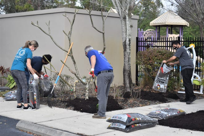 PGT volunteers landscape and mulch Children First's North Port campus on Tuesday.