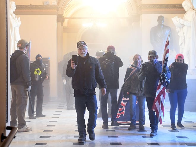 Supporters of U.S. President Donald Trump enter the US Capitol as tear gas fills the corridor on Jan. 6 in Washington, D.C. Demonstrators breached security and entered the Capitol as Congress was preparing to certify the electoral vote in the 2020 presidential election. An FBI court filing says Middleburg residents Rachael Pert and Dana Winn acknowledged being the caped woman and flag-carrying man in the photo.