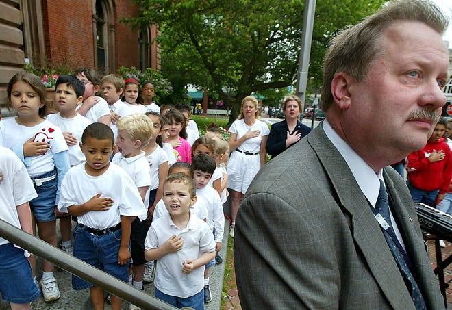 Mayor Frederick Kalisz looks up at the flag as youngsters behind him from the Kempton School in New Bedford sing 'My Country, 'Tis of Thee' during a Flag Day celebration in this 2004 photo.
