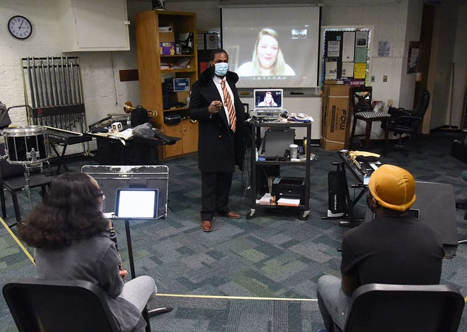 With Rebekah Daley, principal horn of the North Carolina Symphony, visiting by Zoom and appearing on the screen, Kinston High School band director Leonard Palmer introduces her to his musicians during band practice Thursday. Daley will be working with KHS musicians this semester through the N.C. Symphony's Adopt-A-School program. [CONTRIBUTED PHOTO]