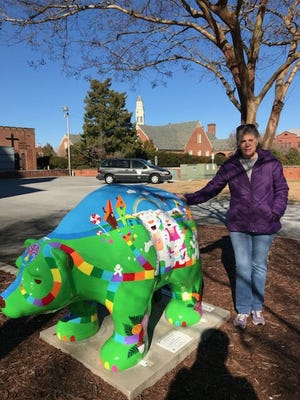 Fairfield Harbour artist and author Deborah Cidboy posed beside the New Bern bear that she recently painted. The bear now stands next to the New Bern City Hall. [CONTRIBUTED PHOTO]