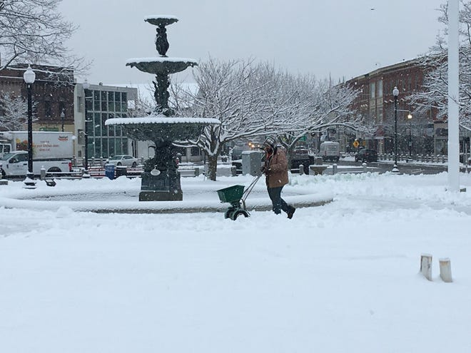 Downtown Taunton was blanketed in snow Wednesday morning, Jan. 27, 2021. Taunton park and rec's Joe Bonaparte treats the sidewalks on the Taunton Green.