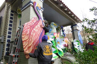 Parade float workers Travis Keene, left, and Joey Mercer position a pelican while fellow crew member Chelsea Kamm, right, looks on while decorating a house in New Orleans on Friday, Jan. 8, 2021. All around the city, thousands of houses are being decorated as floats because the coronavirus pandemic has canceled parades that usually take place on Mardi Gras.